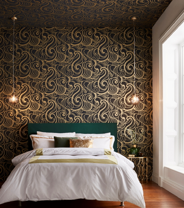 Graham & Brown behang, design Barbara Hulanicki – behang Hula Swirl Gold Noir. (Foto Graham & Brown wallpaper  op DroomHome.nl)